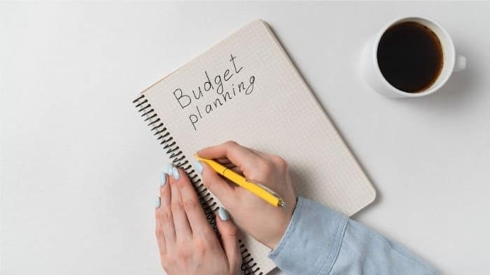 START A SIMPLE MONTHLY BUDGET PLANNER BOOK ON A LEGAL PAD OR NOTEBOOK.